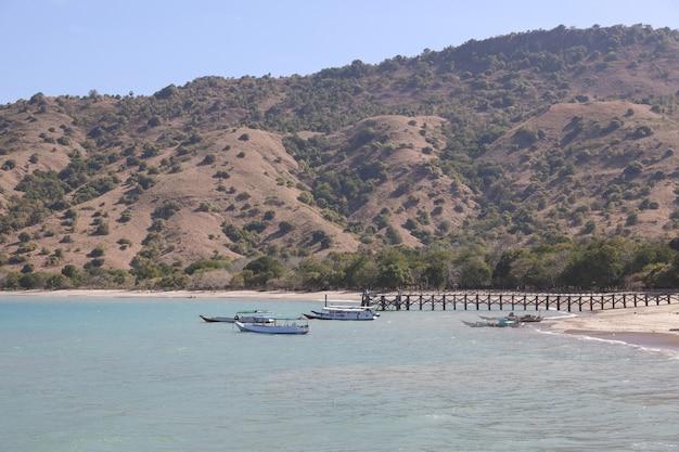 Barche di legno tradizionali che parcheggiano vicino al molo di legno sulla spiaggia di acqua limpida