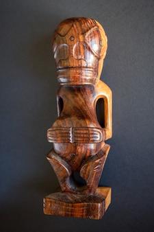Tiki polinesiano tradizionale in legno delle isole marchesi. isolato su uno sfondo scuro