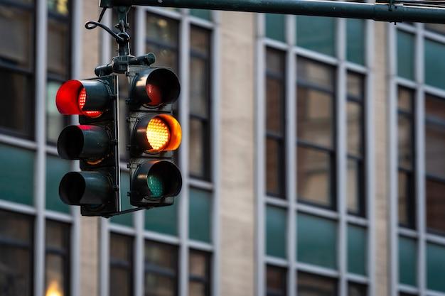 Semaforo con luce rossa sopra manhatan street tra molti grattacieli