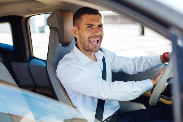 Problemi di traffico. simpatico uomo emotivo che dà un segnale mentre si guida un'auto