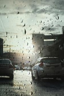 Traffico in una giornata piovosa con luce serale in città, vista attraverso il parabrezza durante la tempesta di pioggia con messa a fuoco selettiva.