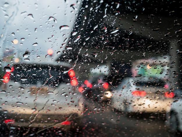 Traffico in una giornata piovosa con vista su strada attraverso il finestrino dell'auto con gocce di pioggia