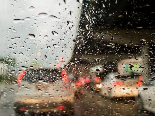 Traffico in una giornata di pioggia con vista sulla strada attraverso il finestrino dell'auto con gocce di pioggia