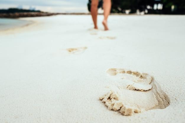Senti i piedi a piedi nudi nella sabbia su una spiaggia
