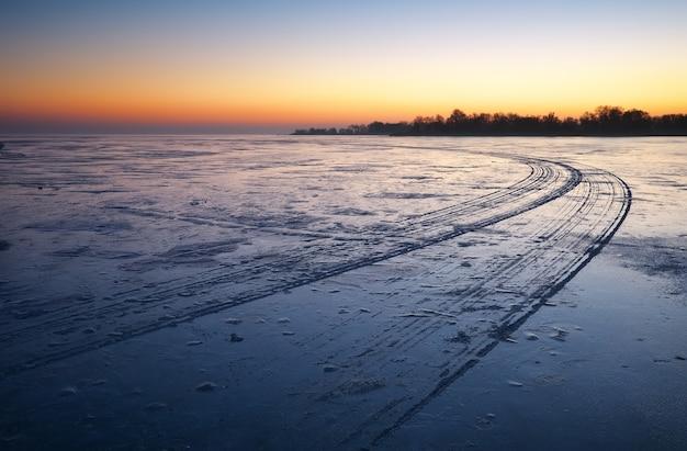 Sentieri sulla superficie del lago ghiacciato. paesaggio invernale paesaggio invernale con lago e cielo infuocato al tramonto.