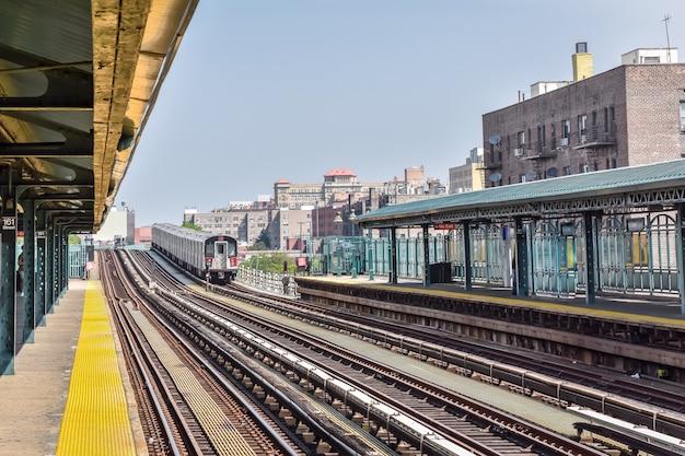 Treno in arrivo alla stazione di new york city. edifici sullo sfondo, paesaggio urbano. concetto di viaggio e transito. manhattan, new york, stati uniti.