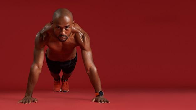 Allenati più duramente per tutta la lunghezza di un forte uomo africano in abbigliamento sportivo facendo flessioni isolate sopra