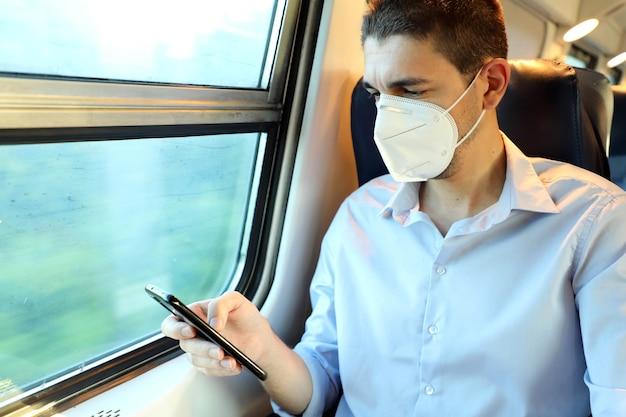Treno passeggeri con maschera protettiva che manda sms sul cellulare