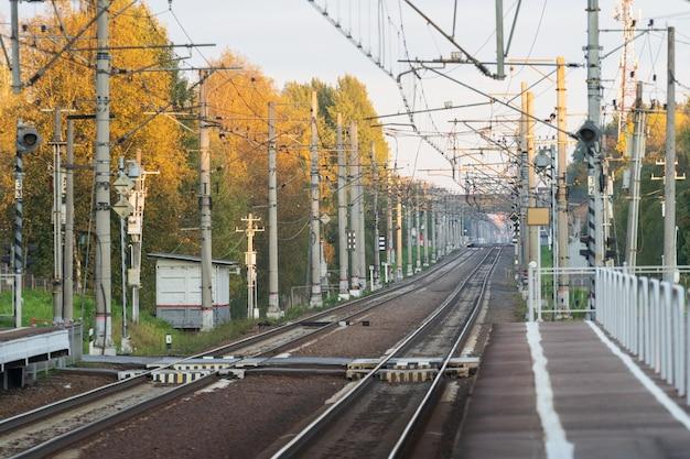Stazione ferroviaria con binari ferroviari prospettiva stagione autunnale della ferrovia ad alta velocità elettrificata