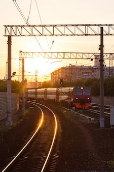 Treno al tramonto. binari ferroviari vicino alla stazione. treno suburbano