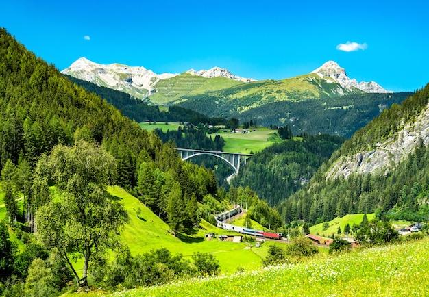 Treno con rimorchi che attraversano le alpi al passo del brennero in austria