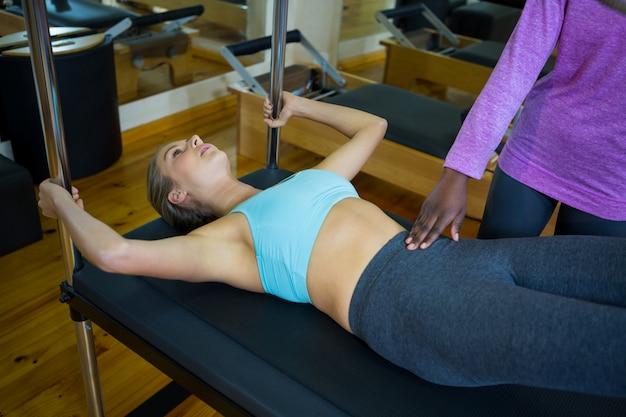 Trainer che assiste la donna con i pilates sul riformatore