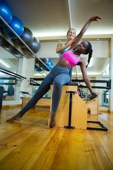Trainer che assiste la donna con la sedia wunda in studio fitness