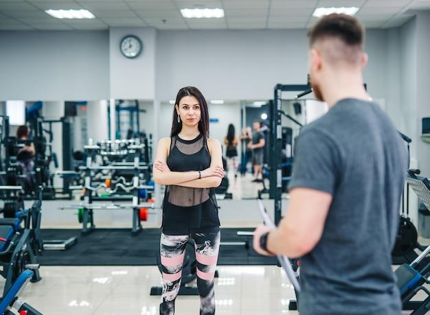 Trainer e cliente discutono dei suoi progressi durante l'esercizio in palestra. istruttore di fitness personale.