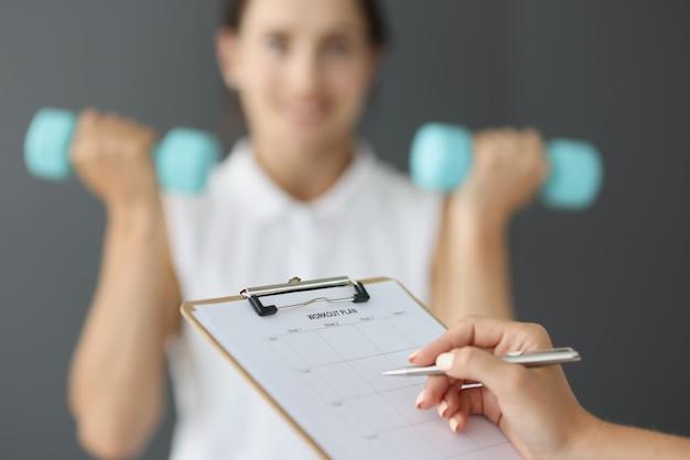 Trainer che compila il piano di allenamento sportivo sullo sfondo di una donna con manubri in primo piano