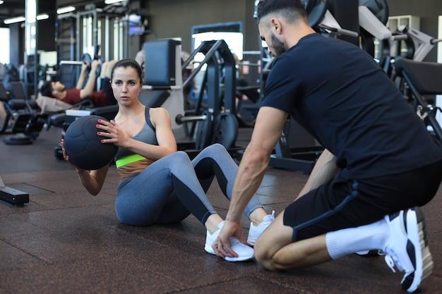 Trainer che aiuta la giovane donna a fare esercizi addominali in palestra.
