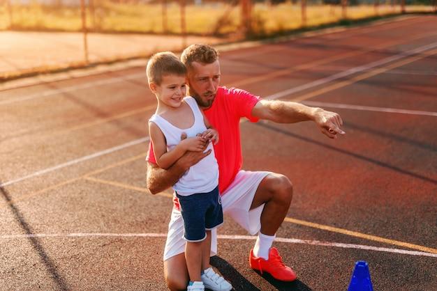 Istruttore che lo abbraccia e che indica con il dito a corte mentre gli spiega gli esercizi.