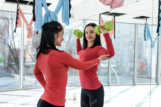 Formazione in forma ragazza insieme. un ritratto di due giovani donne adatte che esercitano sulla forma fisica nella palestra luminosa
