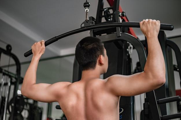 Concetto di palestra di formazione un adolescente di sesso maschile che utilizza un'attrezzatura da palestra tirando entrambe le braccia muscolari contro la macchina.