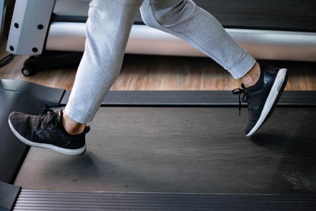 Concetto di palestra di formazione un adolescente maschio che indossa pantaloni lunghi e scarpe da ginnastica nere che camminano su un tapis roulant per un allenamento cardio.