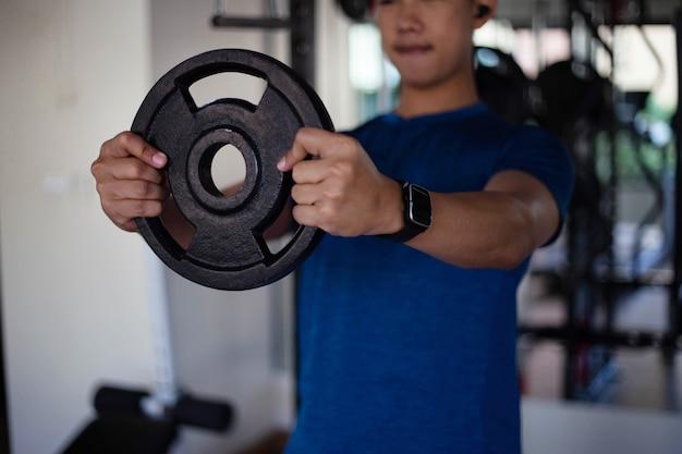 Concetto di palestra di formazione un adolescente maschio muscoloso che usa entrambe le mani che tengono una ruota di ferro pesante.