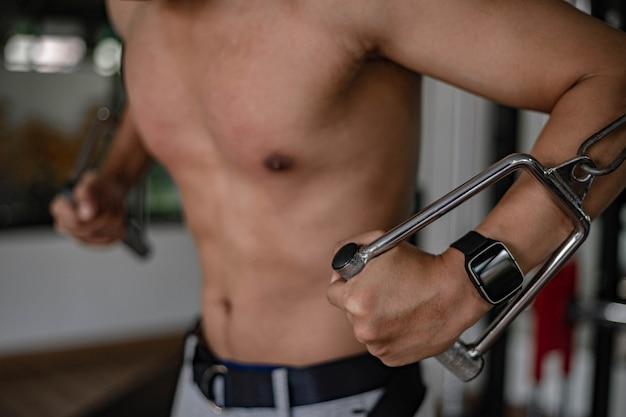 Concetto di palestra di allenamento un adolescente maschio muscoloso che utilizza un'attrezzatura da palestra che ripete la spinta in avanti per sviluppare il seno