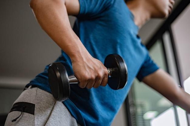 Concetto di palestra di formazione un giovane adulto che usa il suo braccio muscoloso e forte che solleva un manubrio verso l'alto e verso il basso in palestra.