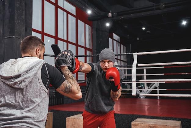 Allenamento duro. atleta muscolare sicuro in guanti rossi che si allenano sulle zampe da boxe con il partner nella palestra di boxe nera black