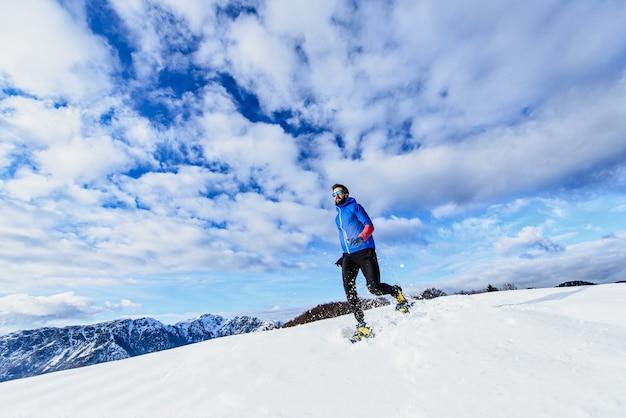 Allenamento sulla neve con le ciaspole da corsa in discesa