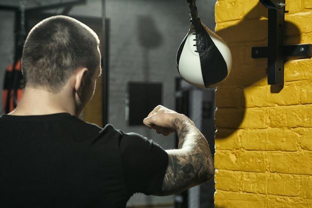Formazione per il successo. inquadratura di un pugile professionista tatuato che si esercita con una speed bag