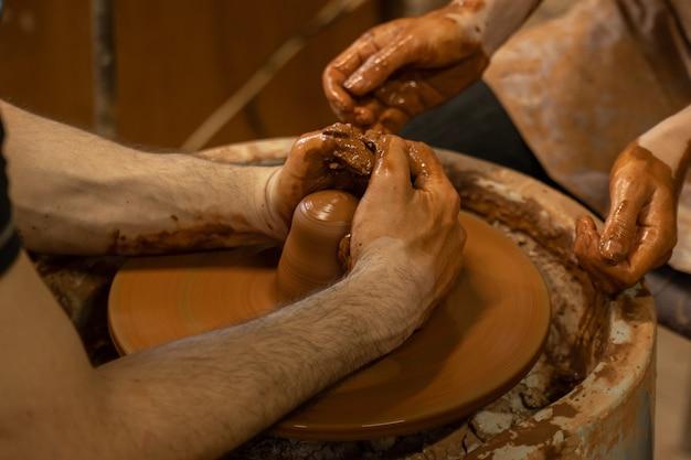 Formazione per il lavoro al tornio un uomo e una donna lavorano insieme con l'argilla