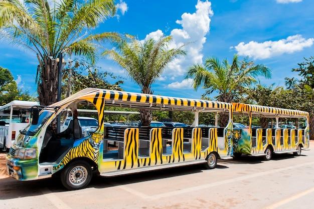 Un tram dipinto con motivi di tigri usati all'interno dello zoo e lo sfondo degli alberi e del cielo.