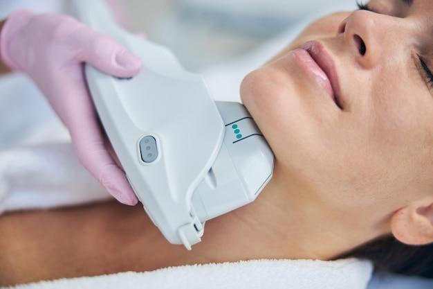 Signora tranquilla che si gode una procedura di ringiovanimento della pelle condotta da un cosmetologo