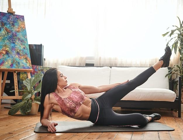 Tranquillo ritratto di una donna sportiva di mezza età sul tappetino posa con la gamba sollevata sullo sfondo del divano e della finestra di casa.