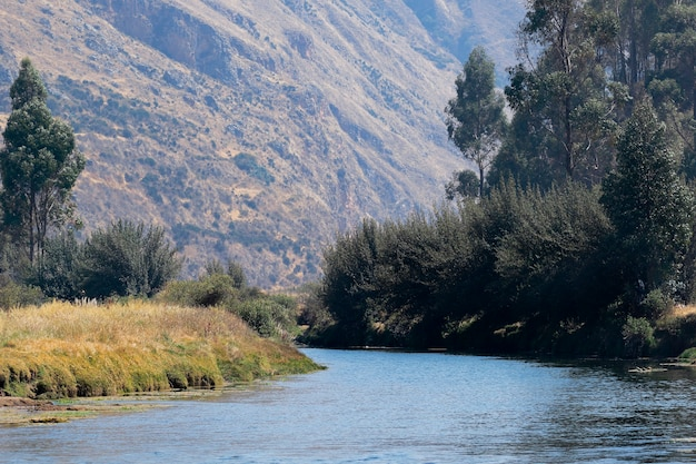 Scena tranquilla di un paesaggio andino vicino al fiume annidato all'interno delle alte montagne