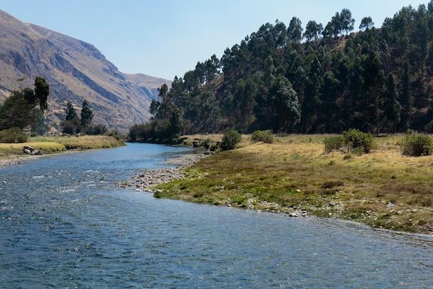 Scena tranquilla di un paesaggio andino vicino al fiume annidato all'interno delle alte montagne Foto Premium