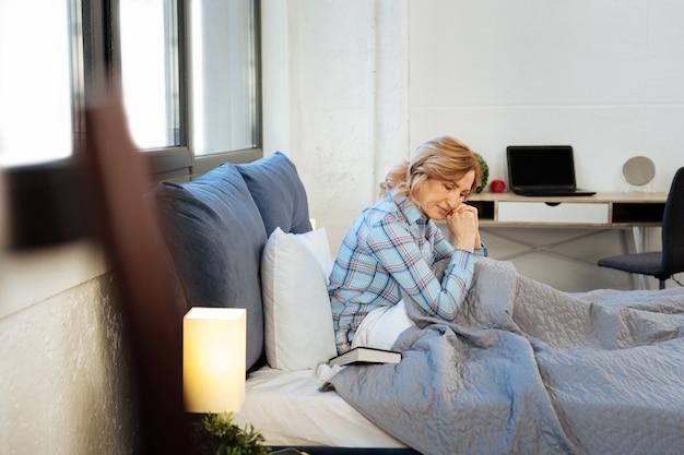 Donna tranquilla. donna religiosa concentrata seduta in un letto disfatto e che trasporta la bibbia durante un'insolita routine mattutina