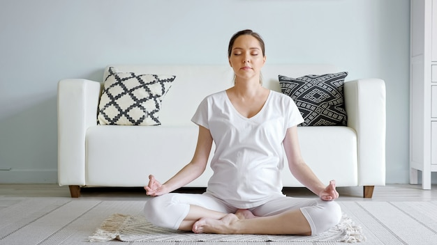 Tranquilla giovane donna incinta in bianco medita seduto nella posa del loto sul tappeto del pavimento vicino al divano di design in una spaziosa stanza a casa primo piano