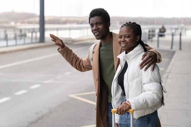 Trasferimento dal terminal coppia africana vicino all'aeroporto con la mano alzata cerca di prendere un taxi dopo l'arrivo