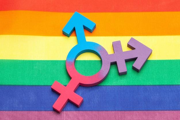 Simbolo transgender e simbolo di genere dell'uomo e della donna sullo sfondo della bandiera arcobaleno dell'orgoglio lgbt.