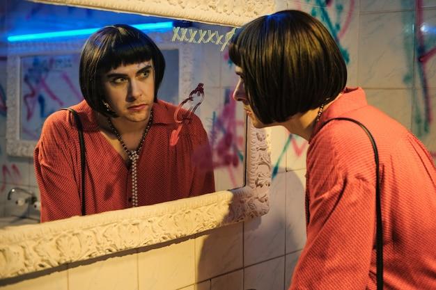 Transgender con parrucca e vestito guardando lo specchio in piedi nella stanza del wc