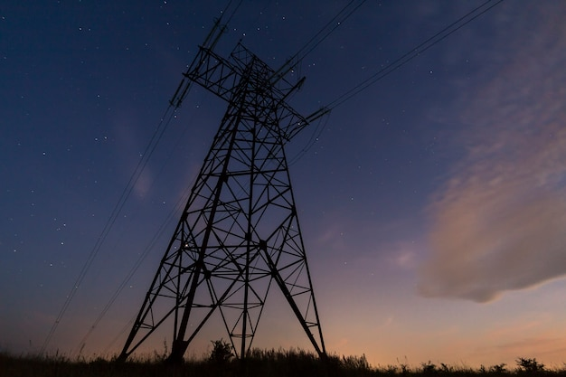 Trasmissione e distribuzione a lunga distanza del concetto di elettricità. vista ad angolo della torre ad alta tensione con le linee di energia elettrica che allungano sulla scena del cielo stellato blu scuro.