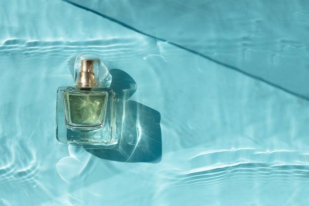 Bottiglia di profumo trasparente in acqua blu con ombre.