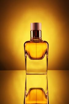 Bottiglia trasparente con profumo di colore oro su un giallo