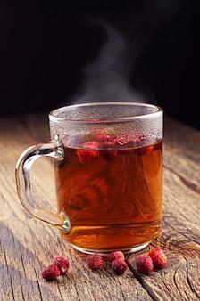 Tazza trasparente di tè caldo con fragoline di bosco su un tavolo di legno vintage
