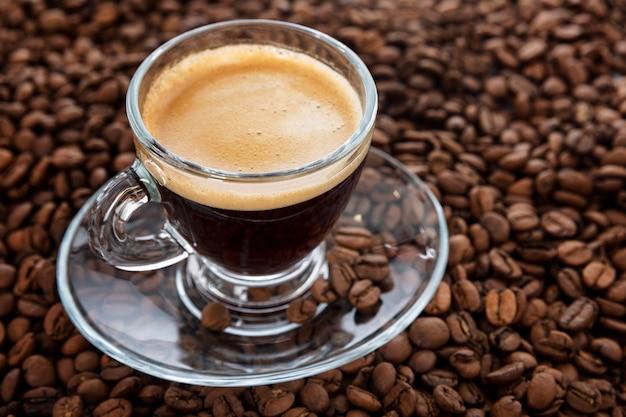 Una tazza trasparente con caffè schiumoso aromatico si trova sui chicchi. avvicinamento.