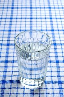 Bicchiere d'acqua sfaccettato trasparente su una tovaglia blu