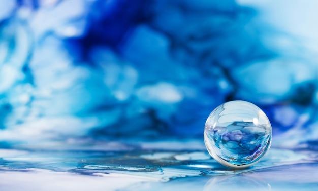 Una palla di vetro trasparente su uno sfondo blu astratto la tecnica dell'inchiostro alcolico