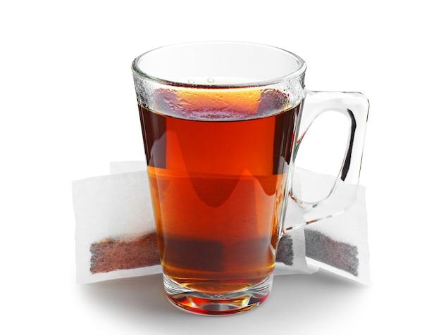 Tazza di vetro trasparente di tè e bustine di tè su bianco
