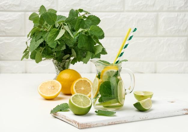 Decanter in vetro trasparente con fette di limone, lime e foglie di menta su un tavolo bianco, detox. dietro gli ingredienti per la bevanda